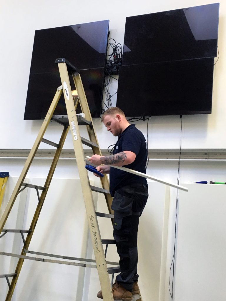 team member servicing video wall